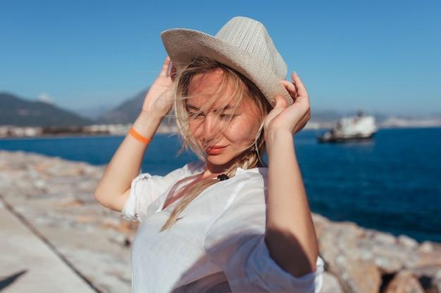 Retrato de uma linda garota com um chapéu e uma camisa branca perto do farol
