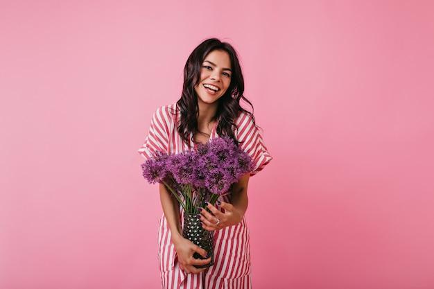 Retrato de uma linda garota com um sorriso encantador. senhora de top listrado, apreciando flores.