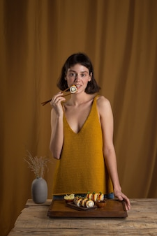 Retrato de uma linda garota comendo sushi roll com salmão usando pauzinhos em um fundo amarelo