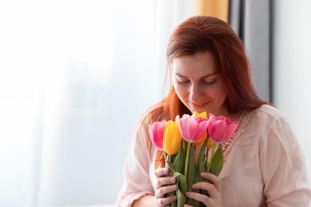 Retrato de uma linda garota de cabelos compridos, segurando um buquê de flores frescas de tulipas nas mãos e cheirando-os no quarto.