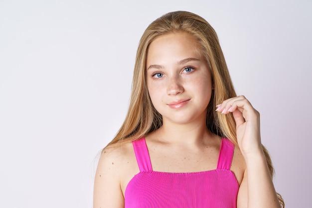 Retrato de uma linda garota de etnia loira caucasiana, posando em um fundo branco com roupas cor de rosa c.