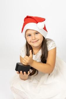 Retrato de uma linda garota de seis anos com chapéu de papai noel segurando um alto-falante de música inteligente e dando os polegares para cima ...