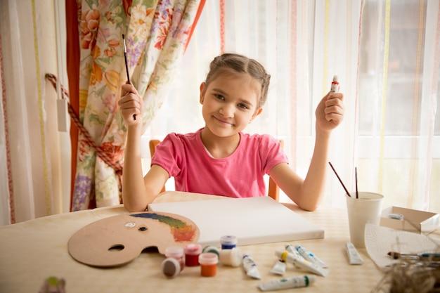 Retrato de uma linda garota desenhando na sala de estar à mesa