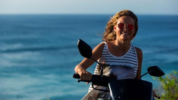 Retrato de uma linda garota dirigindo uma scooter em um penhasco com uma vista incrível para o mar.