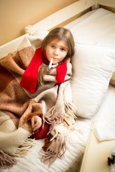 Retrato de uma linda garota doente deitada na cama com o ursinho de pelúcia e medindo a temperatura