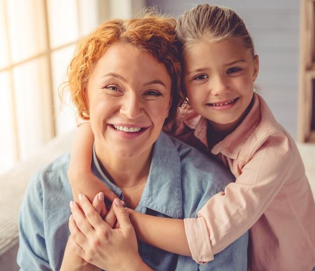 Retrato de uma linda garota e sua linda avó abraçando.