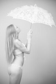 Retrato de uma linda garota em um maiô com guarda-chuva de renda em um fundo cinza