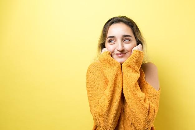 Retrato de uma linda garota em um suéter laranja olhando de lado com expressão pensativa