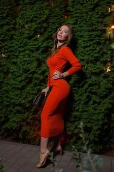 Retrato de uma linda garota em um vestido vermelho cor de vinho em um fundo de folhas de videira no parque