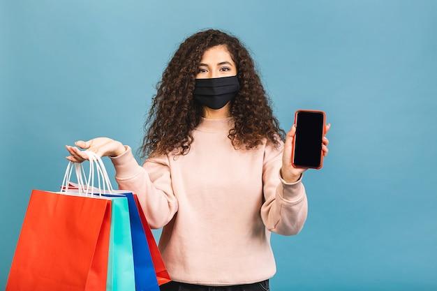 Retrato de uma linda garota encaracolada animada com uma máscara protetora médica no rosto, segurando sacolas de compras isoladas em um fundo rosa