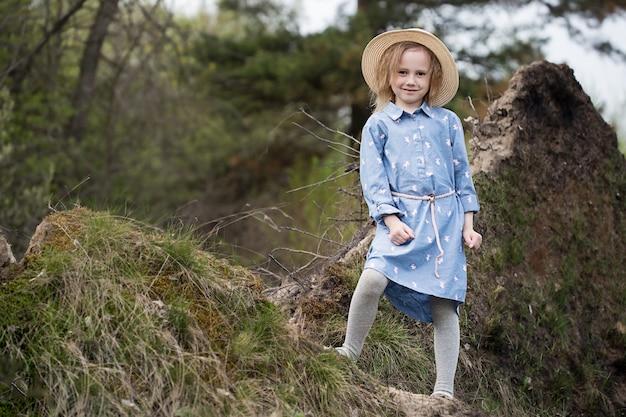 Retrato de uma linda garota engraçada caucasiana de 5 anos de idade em pé ao lado de uma árvore caída com raízes arrebentadas na floresta
