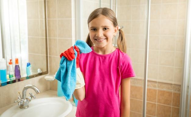 Retrato de uma linda garota fazendo a limpeza, posando com um pano azul