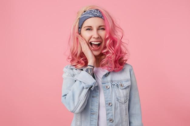 Retrato de uma linda garota feliz com cabelo rosa e mão tatuada, lisonjeada com o elogio, ri e toca a bochecha em pé, vestindo uma camiseta branca e jaqueta jeans.