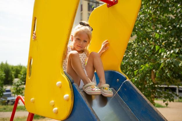 Retrato de uma linda garota fofa em um slide infantil