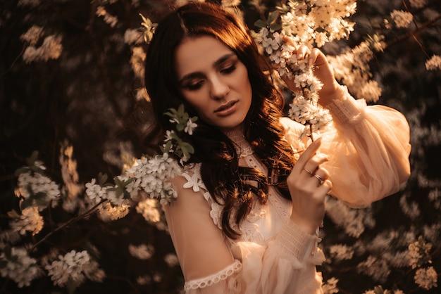 Retrato de uma linda garota. fundo de flores. no contexto de jardins floridos de macieiras.