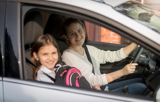 Retrato de uma linda garota indo para a escola com a mãe de carro
