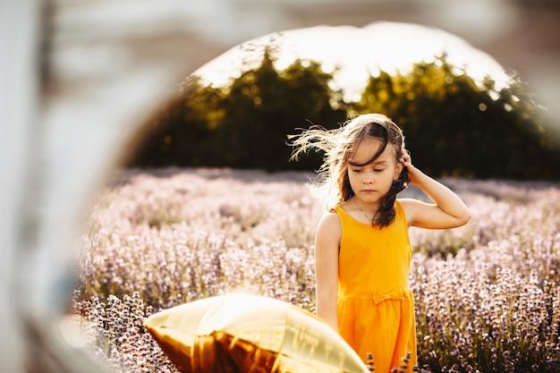 Retrato de uma linda garota jovem olhando pensativamente para baixo brincando com a mão no cabelo enquanto está em um campo de lavanda contra o pôr do sol.