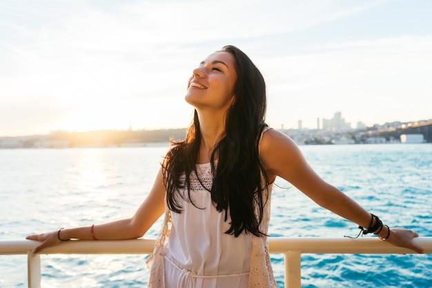 Retrato de uma linda garota latina em um iate ao pôr do sol e risos, uma viagem de balsa, uma viagem de luxo em istambul