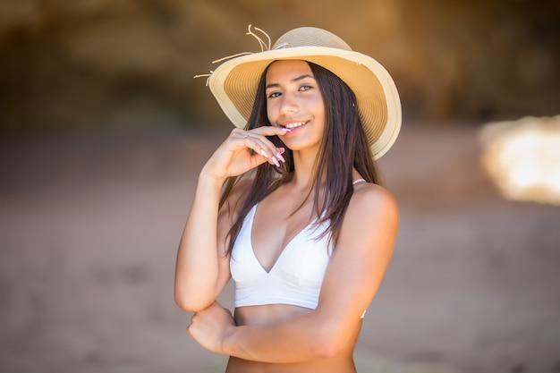 Retrato de uma linda garota latina na praia com chapéu preto, sorriso puro oceano e pedras nas férias de verão