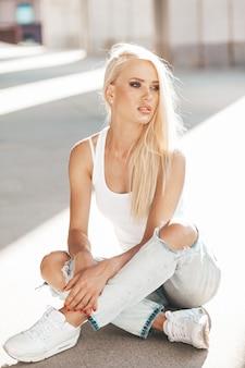 Retrato de uma linda garota loira bonita camiseta branca e calça jeans posando ao ar livre. linda garota sentada no asfalto na rua