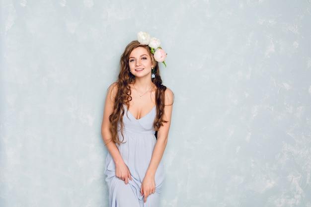 Retrato de uma linda garota loira com cabelo encaracolado de pé em um estúdio com um círculo de peônias. ela usa um vestido de seda azul claro. ela parece terna e doce