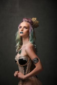 Retrato de uma linda garota loira sexy com cabelos coloridos e maquiagem brilhante no estúdio. conceito de fantasia
