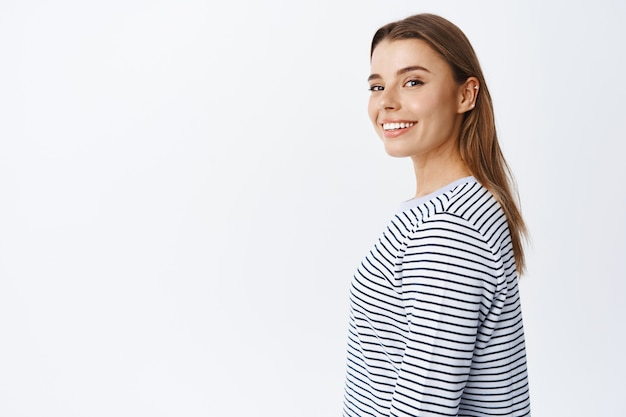 Retrato de uma linda garota loira virando a cabeça para a frente com um sorriso alegre, anunciando produtos de beleza, em pé com roupas casuais contra uma parede branca