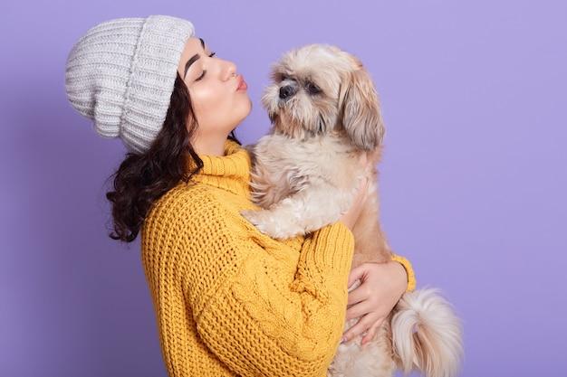 Retrato de uma linda garota mantendo a bela pequinês e quer beijá-lo