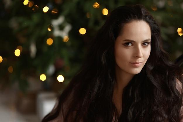 Retrato de uma linda garota modelo com cabelos escuros e maquiagem nude com luzes de natal festivas no ...