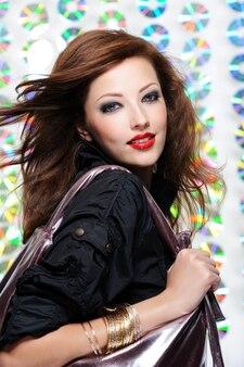 Retrato de uma linda garota moderna segurando uma sacola de compras