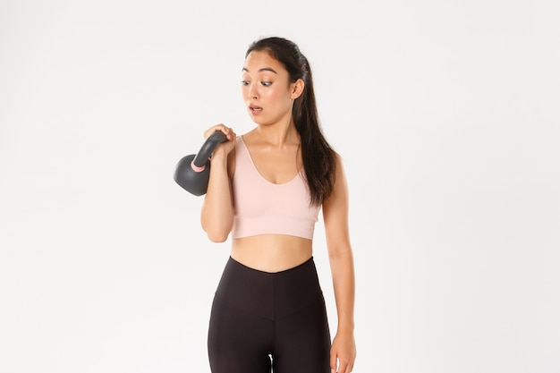 Retrato de uma linda garota morena asiática fitness, inscrever-se em aulas de musculação na academia, surpreso com o peso do kettlebell, em pé