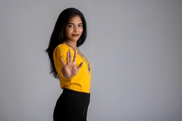 Retrato de uma linda garota mostrando a placa de pare com as palmas das mãos em um cinza