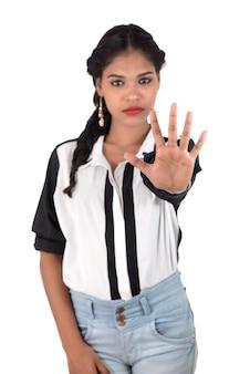 Retrato de uma linda garota mostrando a placa de pare com as palmas das mãos isoladas em um fundo branco