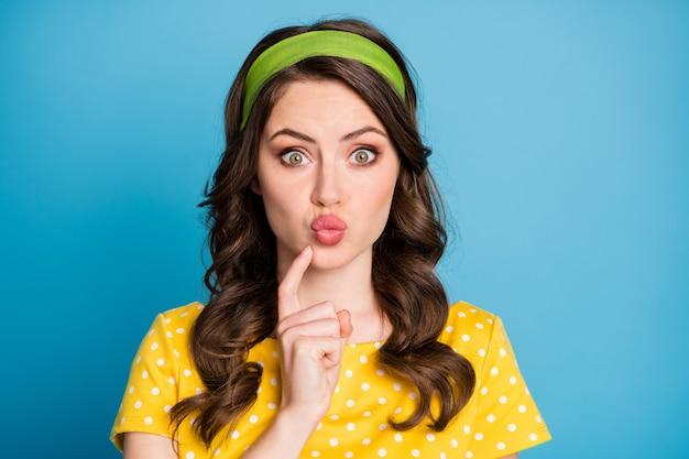 Retrato de uma linda garota olhando para a câmera com lábios amuados tocando o queixo do dedo isolado sobre o fundo de cor azul