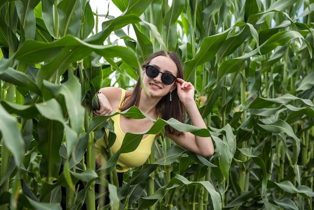 Retrato de uma linda garota posando em um campo de milho verde, aproveite o verão