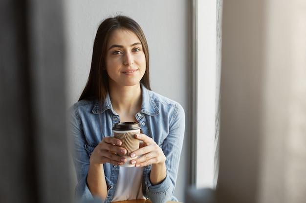 Retrato de uma linda garota relaxada com cabelos escuros na camiseta branca sob a camisa jeans, sorrindo enquanto bebe a xícara de café.