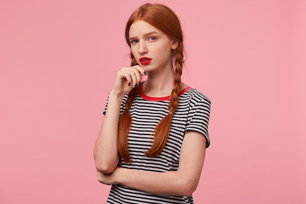 Retrato de uma linda garota ruiva com duas tranças mantém o punho perto do queixo e parece cético, com suspeita e desconfiança, questionável, isolado na parede rosa