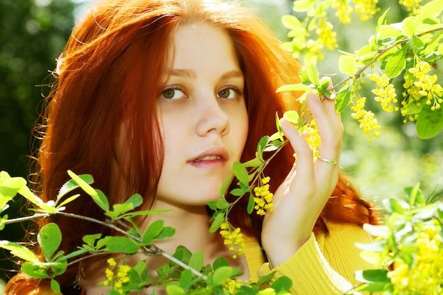 Retrato de uma linda garota ruiva sorridente, ao ar livre