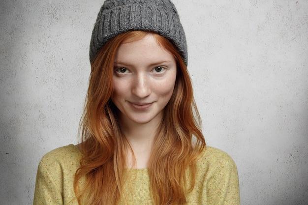 Retrato de uma linda garota sardenta com longos cabelos ruivos e um sorriso encantador e fofo, usando um chapéu cinza estiloso, olhando e sorrindo em pé contra a parede