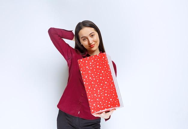 Retrato de uma linda garota segurando a caixa de presente, sobre uma parede branca.