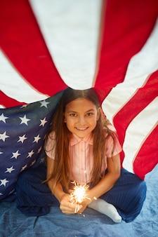 Retrato de uma linda garota segurando luzes cintilantes sorrindo, coberto pela bandeira americana