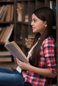 Retrato de uma linda garota segurando um livro