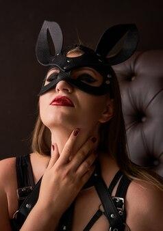 Retrato de uma linda garota sensual na máscara de coelho preto da modelo vestindo um maiô preto e cinto