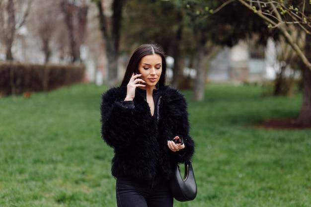 Retrato de uma linda garota sorridente, com longos cabelos escuros, vestindo preto. jovem mulher usando telefone celular