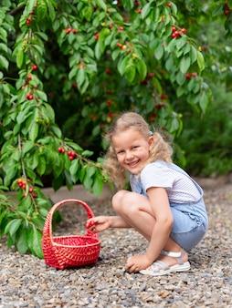 Retrato de uma linda garota sorridente com uma cesta de cerejas.