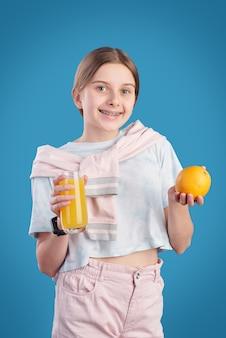 Retrato de uma linda garota sorridente em pé e segurando um copo de suco de laranja