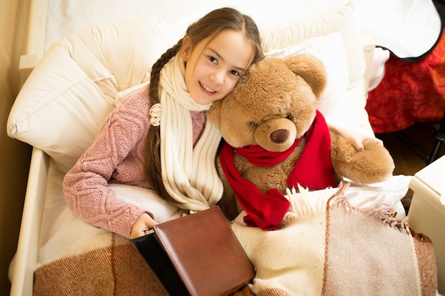 Retrato de uma linda garota sorridente lendo livro com ursinho de pelúcia na cama