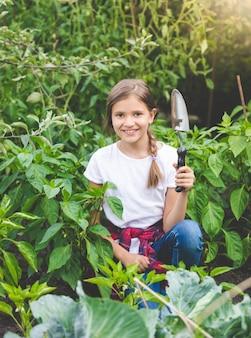 Retrato de uma linda garota sorridente posando com uma espátula no jardim florido
