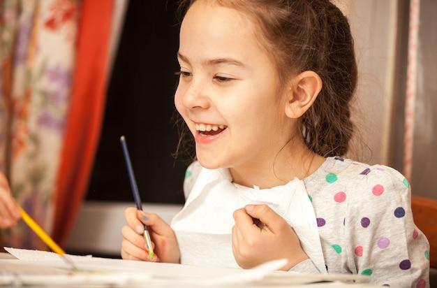 Retrato de uma linda garota sorridente segurando um pincel