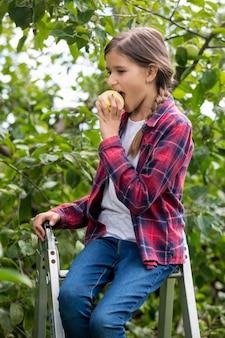 Retrato de uma linda garota sorridente, sentada na escada e mordendo uma maçã fresca